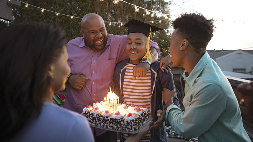 African-American family celebrating their son's graduation with cake on their backyard deck