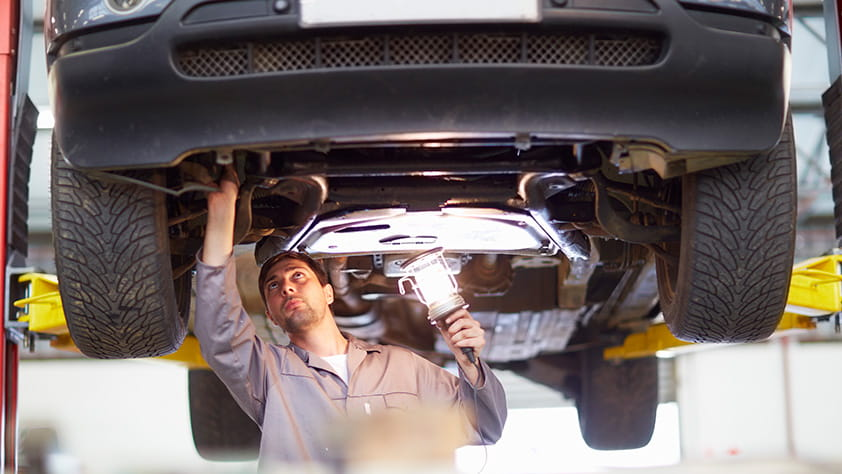 Auto Technician Inspecting Undercarriage of Car