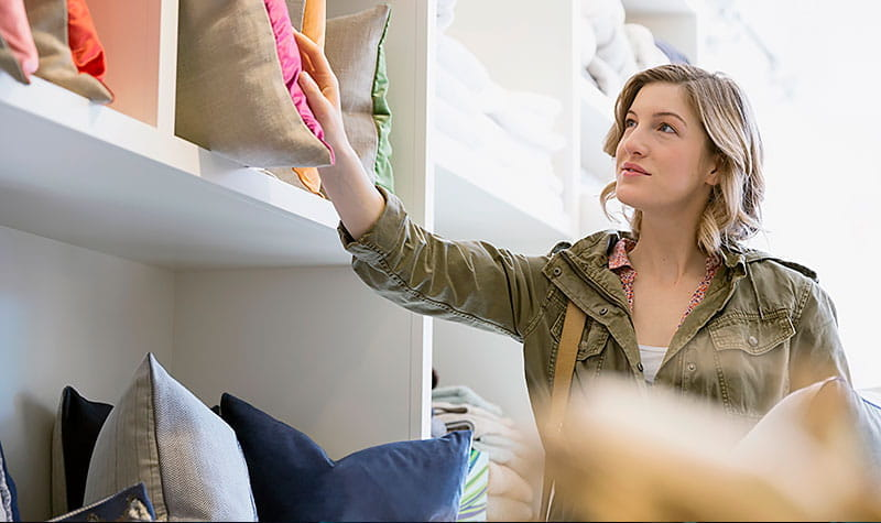 Woman shopping, looking at decorative pillows