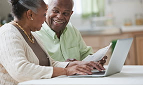Senior African-American husband and wife using their laptop and reading a paper document