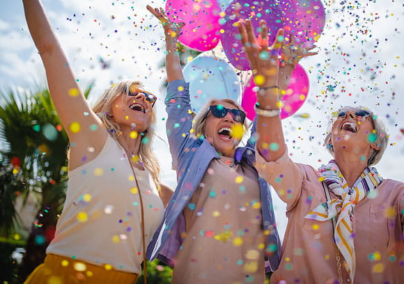 Excited Women Celebrating Outdoors with Colorful Confetti and Balloons
