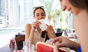 Female Friends Reviewing Check at Restaurant