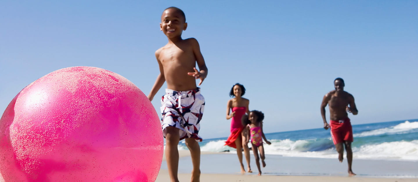 Family Playing on the Beach with a Large Pink Ball