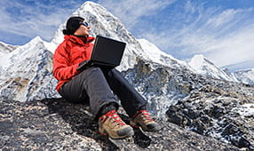Woman with Laptop Wearing an Orange Parka Sitting on Mountain Rocks