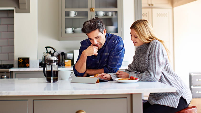 Young couple using a digital tablet while sitting at their kitchen table at home