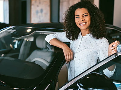 Smiling woman getting into her new car