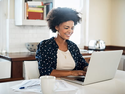 Woman seated at desk working on laptop